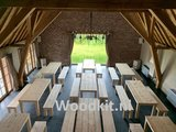 Steigerhout tafels in een feestzaal in Belgie